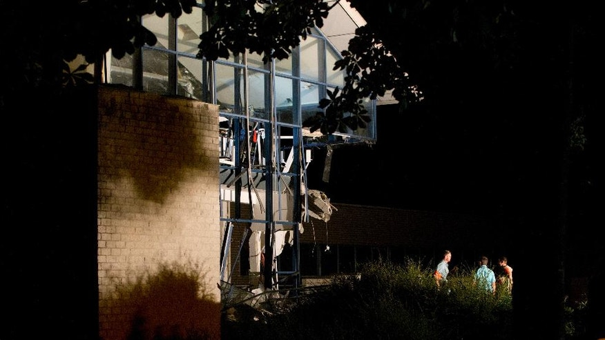 Police and firefighters inspect the scene of a blast at a sports complex in Chimay, Belgium, Friday, Aug. 26, 2016. One person is reported to have been killed and at least two injured in an accidental explosion at a sports center near the French border. (AP Photo/Virginia Mayo)