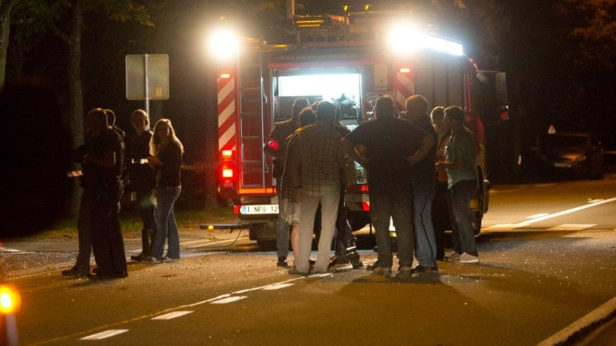 Rescue workers and others stand near an emergency vehicle at the scene of a blast at a sports complex in Chimay, Belgium, Friday, Aug. 26, 2016. One person is reported to have been killed and at least two injured in an accidental explosion at a sports center near the French border. (AP Photo/Virginia Mayo)