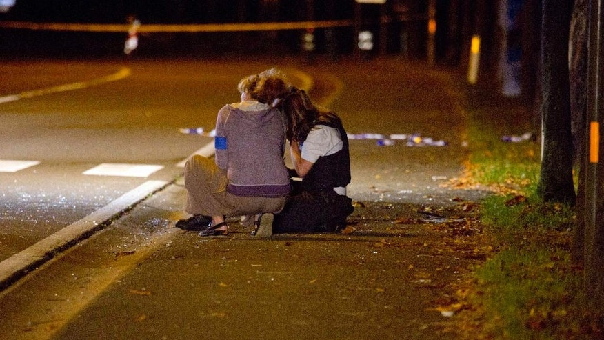 Two police officers sit on the sidewalk near the scene of a blast at a sports complex in Chimay, Belgium, Friday, Aug. 26, 2016. One person is reported to have been killed and at least two injured in an accidental explosion at a sports center near the French border. (AP Photo/Virginia Mayo)