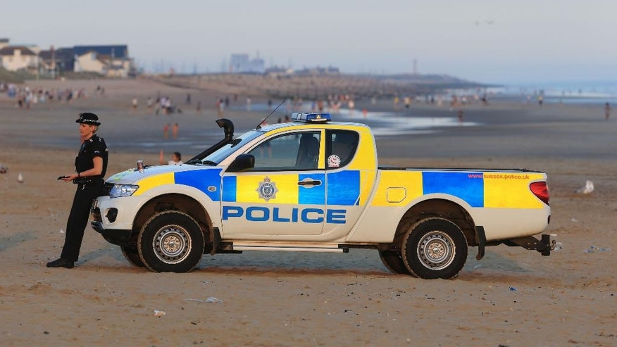 Police officers on Camber Sands near Rye, East Sussex, England, after three men died after being pulled from the sea on the hottest day of the year, Wednesday Aug. 24, 2016. Emergency teams were called to reports of the three needing urgent medical aid at Camber Sands according to reports from the Maritime and Coastguard Agency (MCA). ( Gareth Fuller / PA via AP)