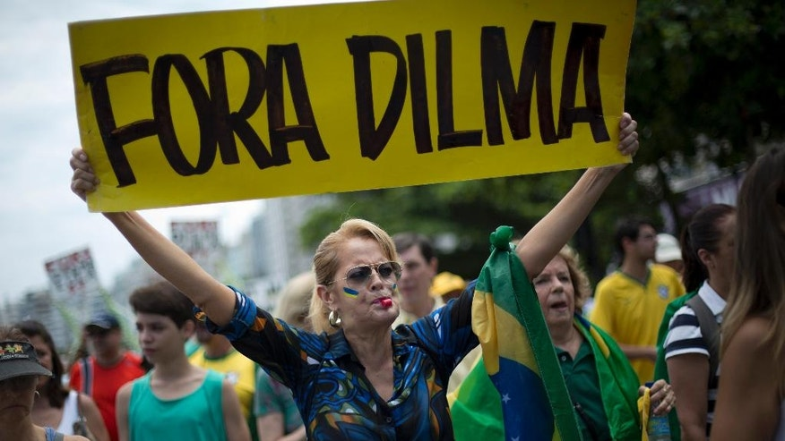 """FILE - In this Dec. 13, 2015 file photo, a woman holds a sign that reads in Portuguese; """"Dilma Out"""" during a demonstration in favor of the impeachment of Brazil's President Dilma Rousseff, on Copacabana beach in Rio de Janeiro, Brazil. Just days after the Rio Olympics ended, Brazilian senators are now gearing up for a final decision on whether to permanently remove Rousseff from office. (AP Photo/Silvia Izquierdo, File)"""
