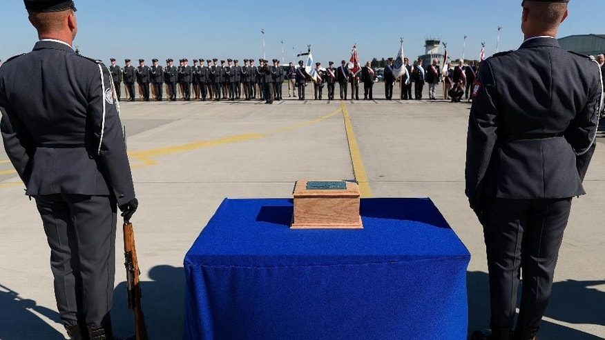 A wooden urn with the ashes of Polish fighter ace Capt. Kazimierz Sporny, credited with downing at of least five enemy planes in the Battle of Britain, is greeted with military honors at the Krzesiny Air Base in Poznan, Poland on Thursday, August 25, 2016, after being brought from London for a military burial in his hometown. The burial ceremony of Sporny, who died in Britain in 1949 was part of ceremonies honoring Poland's Air Force at a time when the conservative government attaches great importance to defense because of Russia's actions in western Ukraine. (AP Photo) Poland Out