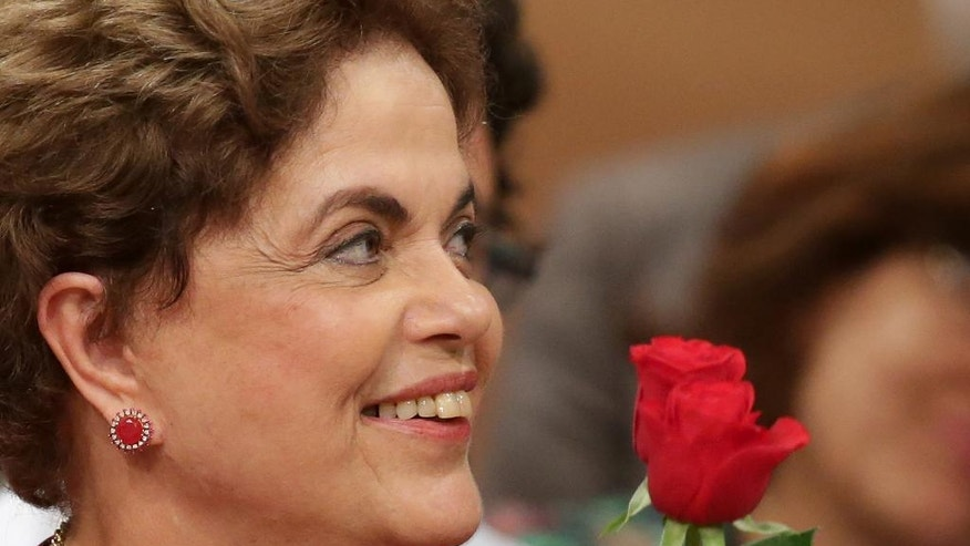 Brazil's suspended President Dilma Rousseff smiles during a rally in Brasilia, Brazil, Wednesday, Aug. 24, 2016. Brazil's Senate braces for a final showdown in a trial that could overthrow President Rousseff after months of lengthy proceedings in Congress. She is accused of breaking fiscal laws, in managing the federal budget as her government ran out of resources. (AP Photo/Eraldo Peres)