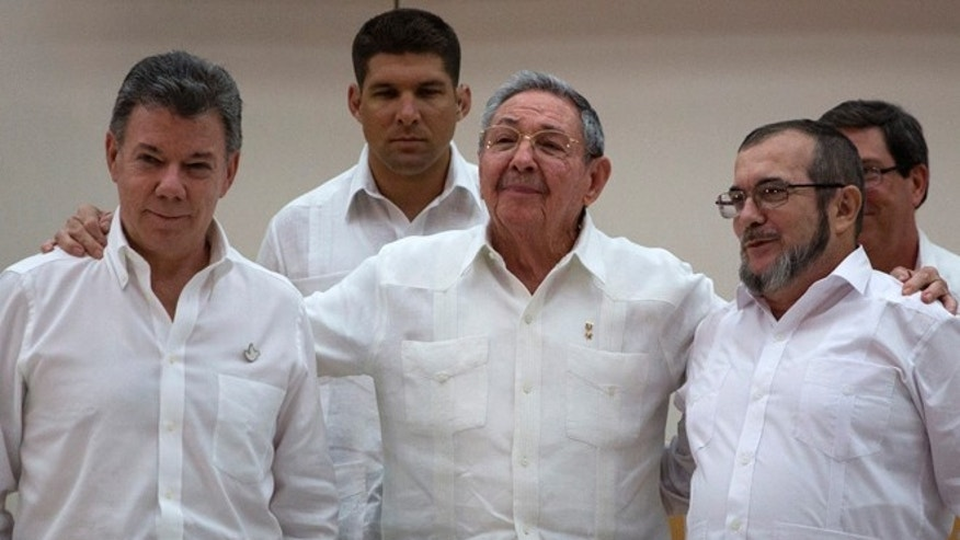 In this Sept. 23, 2015 file photo, Cuba's President Raul Castro, center, stands with Colombian President Juan Manuel Santos, left, and Commander the Revolutionary Armed Forces of Colombia or FARC, Timoleon Jimenez , in Havana, Cuba.