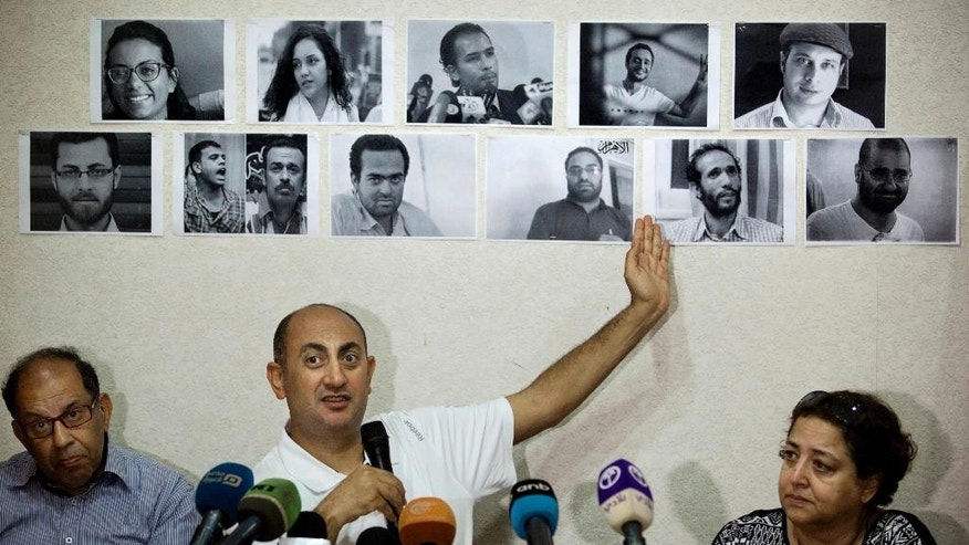 FILE - In this Wednesday, June 22, 2016 file photo, Egyptian lawyer and former presidential candidate Khaled Ali points to photos of jailed activists, who were arrested during protests over two disputed Red Sea islands, including Egyptian rights lawyer Malek Adly, top row third right, during a press conference, in Cairo, Egypt. An Egyptian court has ordered on Thursday, Aug. 25, 2016 the release of the prominent rights lawyer held in solitary confinement for the past three months after he challenged in court a decision by the country's president to hand over two Red Sea islands to Saudi Arabia. (AP Photo/Amr Nabil, File)