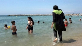 FILE - In this Aug. 4 2016 file photo made from video, Nissrine Samali, 20, gets into the sea wearing a burkini, a wetsuit-like garment that also covers the head, in Marseille, southern France. Burkinis vs. bikinis. Beneath the clash over how to dress, or undress, on the beaches of France simmers an issue that for decades has divided the nation, and grown more complex in this time of terrorism.(AP Photo, File)