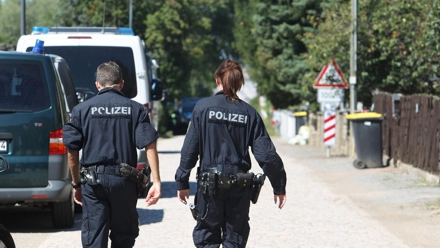 """Police officers walk along a road in Reuden, Germany,Thursday Aug. 25,  2016.  Three people have been wounded in an armed standoff between police and members of a group that denies the legitimacy of the modern German state in Reuden, eastern Germany. A spokeswoman for police in the eastern state of Saxony-Anhalt says the shootout happened while about 100 police, including a tactical response team, were trying to enforce an eviction order against a 41-year-old """"Reich citizen"""" early Thursday.  (Sebastian Willnow/dpa via AP)"""