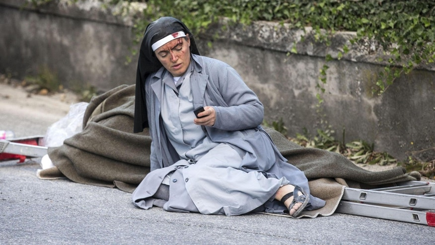 Aug. 24, 2016: Sister Marjana,  from Albania, checks her mobile phone as she lies near a victim laid on a ladder following an earthquake in Amatrice, Italy.