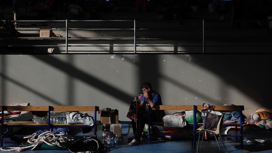A man sits on a bench after spending the night in a makeshift camp set up inside a gymnasium following an earthquake, in Amatrice, central Italy, Thursday, Aug. 25, 2016. The civil protection agency set up tent cities around the affected towns to accommodate the homeless, 1,200 of whom took advantage of the offer to spend the night, civil protection officials said Thursday. In Amatrice, some 50 elderly and children spent the night inside a local sports facility. (AP Photo/Alessandra Tarantino)