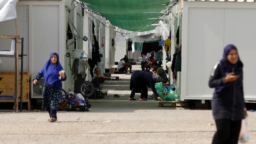People sit outside their container houses at a refugee camp which houses about 3,200 refugees and migrants, in the western Athens' suburb of Skaramagas, Thursday, Aug. 25, 2016. Numbers arriving in Greece have dropped dramatically since the March agreement with Turkey, but over 58,000 people remain stranded in the country, most in army-built camps on the mainland and over 9,000 refugees are receiving hotel vouchers or live in vacant apartments. (AP Photo/Thanassis Stavrakis)