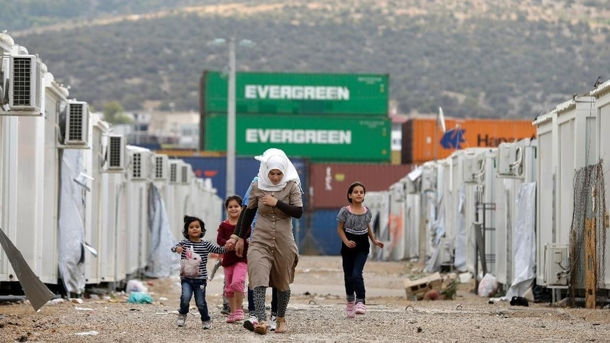 People walk at a refugee camp which houses about 3,200 refugees and migrants, in the western Athens' suburb of Skaramagas, Thursday, Aug. 25, 2016. Numbers arriving in Greece have dropped dramatically since the March agreement with Turkey, but over 58,000 people remain stranded in the country, most in army-built camps on the mainland and over 9,000 refugees are receiving hotel vouchers or live in vacant apartments. (AP Photo/Thanassis Stavrakis)