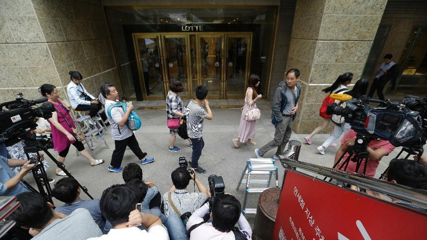 People pass by Lotte Group office in Seoul, South Korea, Friday, Aug. 26, 2016. Lotte Group says its vice chairman has been found dead as authorities widen a probe into corruption at South Korea's fifth-largest business group. (AP Photo/Ahn Young-joon)