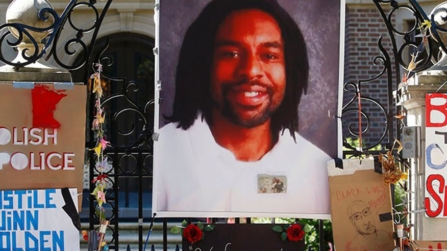 A memorial including a photo of Philando Castile adorns the gate to the governor's residence in St. Paul, Minn.