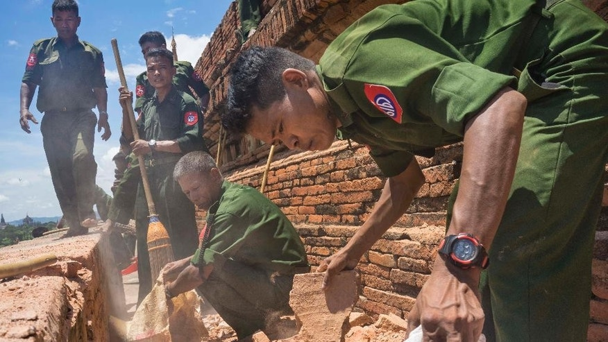 Myanmar Military personnel examine the Htilominlo Pagoda in Bagan, Myanmar, Thursday, Aug. 25, 2016.  Using brooms and their hands, soldiers and residents of the ancient Myanmar city famous for its historic Buddhist pagodas began cleaning up the debris Thursday from a powerful earthquake that shook the region and damaged nearly 200 temples. (AP Photo/Hkun Lat)