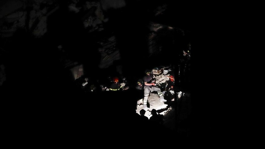Rescuers search amid the rubble following an earthquake in Pescara Del Tronto, Italy, Thursday, Aug. 25, 2016. A strong earthquake struck on Wednesday and was felt across a broad swath of central Italy, including Rome, where residents woke to a long swaying followed by aftershocks. (AP Photo/Gregorio Borgia)