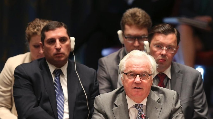 File-This July 20, 2015, file photo shows Russian Ambassador to the United Nations Vitaly Churkin speaking after a vote in the Security Council at U.N. headquarters. Churkin said Thursday, Aug. 25, 2016, there doesn't have to be a confrontation with the United States over a report that blames the Syrian government and Islamic State militants for carrying out chemical attacks in the conflict-torn country. (AP Photo/Seth Wenig, File)