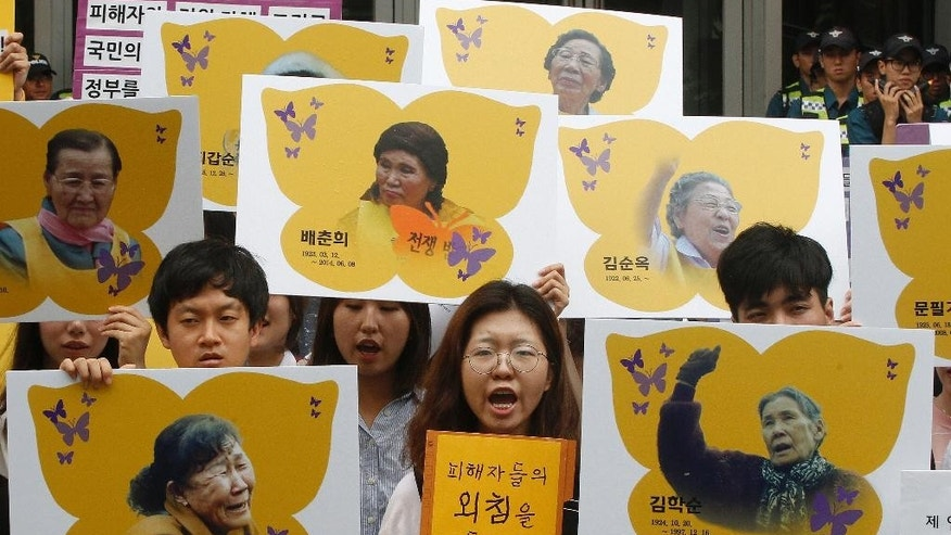 FILE - In this Thursday, July 28, 2016 file photo, protesters hold the portraits of the former South Korean sex slaves who were forced to serve for the Japanese military in World War II, during a rally against the establishment of the Japanese government-funded Reconciliation and Healing Foundation in Seoul, South Korea. South Korea said on Thursday, Aug. 25, 2016, surviving South Korean women who were forced into sexual slavery by Japan's military in World War II will be eligible to receive 100 million won (about $90,000) each from a foundation that will be funded by the Japanese government. (AP Photo/Ahn Young-joon. File)