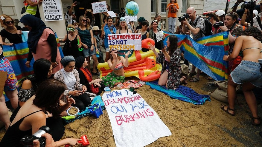 """Activists protest outside the French embassy, during the """"wear what you want beach party"""" in London, Thursday, Aug. 25, 2016. The protest is against the French authorities clampdown on Muslim women wearing burkinis on the beach. Writing on the sign reads: 'No to Islamophobia, yes to Burkinis.' (AP Photo/Frank Augstein)"""