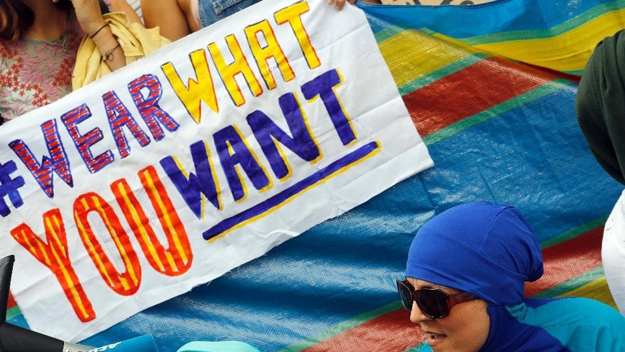 """An activist protests outside the French embassy during, the """"wear what you want beach party"""" in London, Thursday, Aug. 25, 2016. The protest is against the French authorities clampdown on Muslim women wearing burkinis on the beach. (AP Photo/Frank Augstein)"""