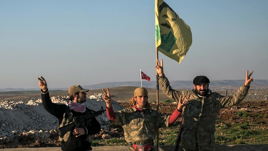 FILE - In this Feb. 22, 2015 file photo, Syrian Kurdish militia members of the YPG make a V-sign next to a drawing of Abdullah Ocalan, jailed Kurdish rebel leader, in Esme village in Aleppo province, Syria. A Turkish military expedition into Syria has threatened a Kurdish political project just as Kurdish forces seemed on the verge of connecting their northern Syrian zones. It is the first Turkish ground intervention in the course of the Syria war, now in its sixth year, and it underscores how seriously Turkey is taking Kurdish autonomy next door. (Mursel Coban/Depo Photos via AP, File)