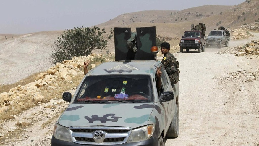 FILE - In this May 20, 2015 file photo released by the Kurdish fighters of the People's Protection Units (YPG), which has been authenticated based on its contents and other AP reporting, Kurdish fighters of the YPG stand on their vehicles on their way to battle against the Islamic State, near Kezwan mountain, northeastern Syria. A Turkish military expedition into Syria has threatened a Kurdish political project just as Kurdish forces seemed on the verge of connecting their northern Syrian zones. It is the first Turkish ground intervention in the course of the Syria war, now in its sixth year, and it underscores how seriously Turkey is taking Kurdish autonomy next door. (The Kurdish fighters of the People's Protection Units via AP, File)