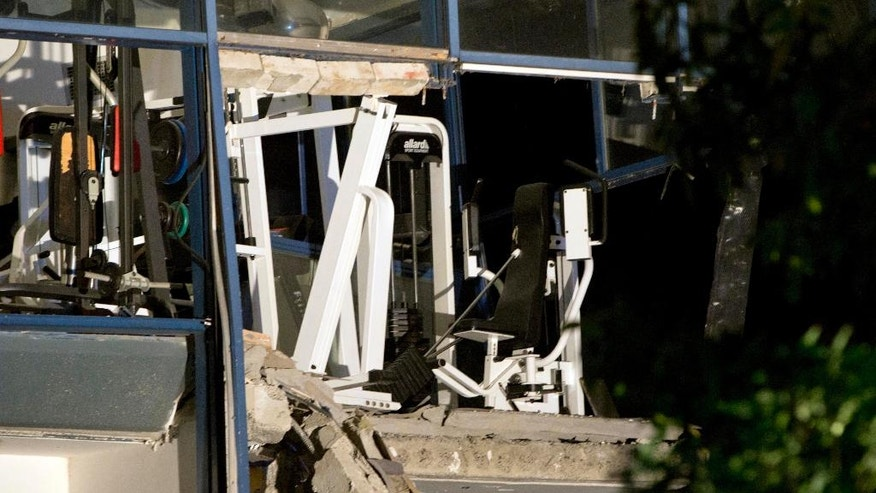 A fitness machine stands on a damaged concrete structure at the scene of a blast at a sports complex in Chimay, Belgium, Friday, Aug. 26, 2016. One person is reported to have been killed and at least two injured in an accidental explosion at a sports center near the French border. (AP Photo/Virginia Mayo)