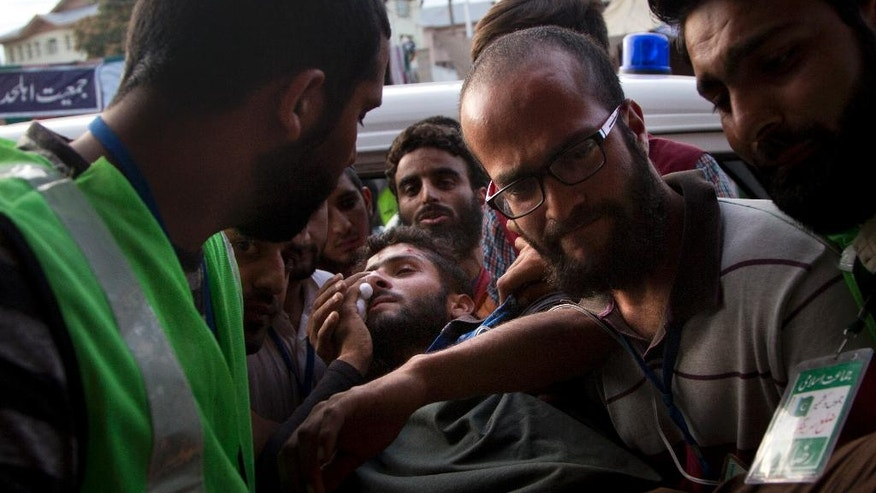 An injured Kashmiri man is brought for treatment to a hospital in Srinagar, Indian controlled Kashmir, Friday, Aug. 26, 2016. Police in Kashmir say a young man was killed and dozens of other civilians were wounded in new protests against Indian rule in the disputed Himalayan region. Police said thousands of Kashmiris defied harsh security restrictions and joined the protests after Friday Muslim prayers.(AP Photo/Dar Yasin)