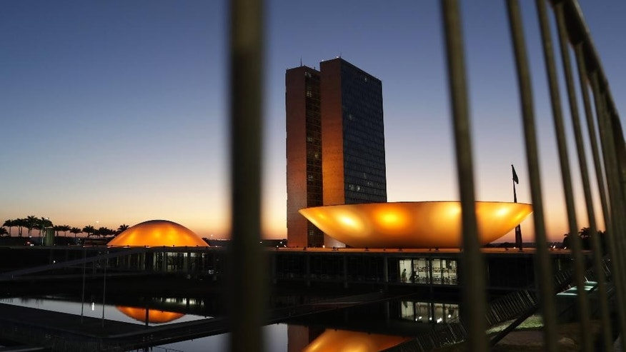 The domes of the the National Congress building, designed by the late Brazilian Oscar Niemeyer, are illuminated as the sun rises on the first day of the impeachment trial of suspended President Dilma Rousseff, in Brasilia, Brazil, Thursday, Aug. 25, 2016. Brazil's Senate on Thursday began deliberating whether to permanently remove Rousseff from office, the final step in a leadership fight that has paralyzed Congress and cast a pall over a nation in the midst of a severe recession. (AP Photo/Eraldo Peres)