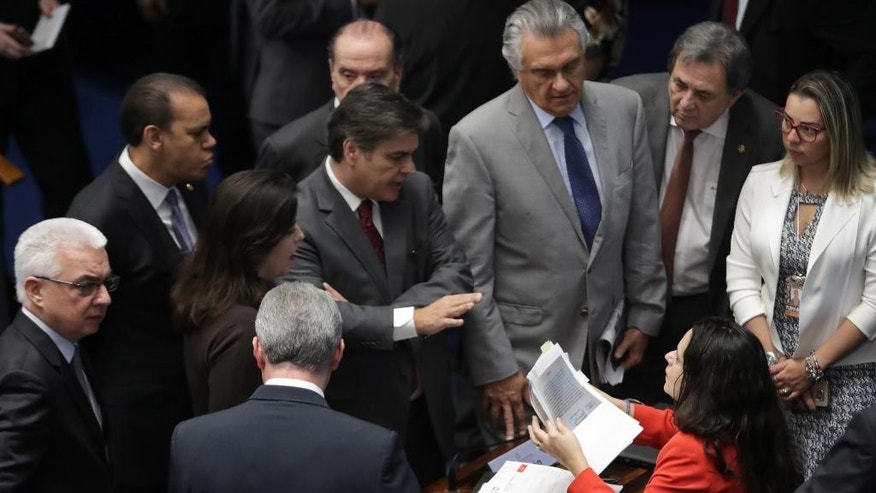 "Lawyer Janaina Paschoal, sitting, talks with senators who support the impeachment of suspended President Dilma Rousseff, during the impeachment trial in Brasilia, Brazil, Friday, Aug. 26, 2016. The second day of the trial turned into a yelling match and was temporarily suspended on Friday after the head of Senate declared ""stupidity is endless"" and sharply criticized a colleague who had questioned the body's moral authority. (AP Photo/Eraldo Peres)"