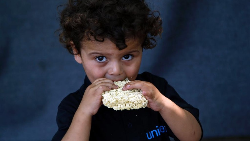 A migrant child eats at a makeshift camp for migrants in Horgos, Serbia, meters away from Serbia's border with Hungary, Thursday, Aug. 25, 2016. Officials say Hungary's police could join the Serbian troops patrolling the Balkan country's border with Macedonia or Bulgaria to help curb the influx of migrants trying to reach the European Union. (AP Photo/Darko Vojinovic)