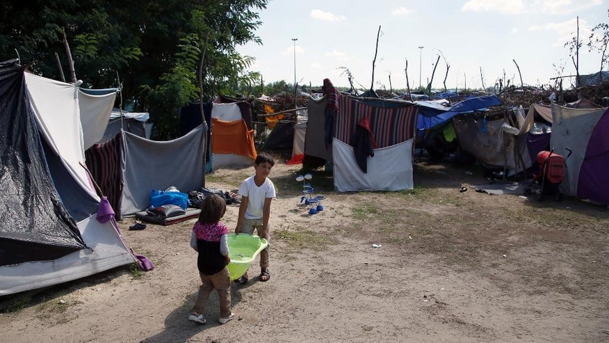 Children carry water at a makeshift camp for migrants in Horgos, Serbia, meters away from the Serbia's border with Hungary, Thursday, Aug. 25, 2016. Officials say Hungary's police could join the Serbian troops patrolling the Balkan country's border with Macedonia or Bulgaria to help curb the influx of migrants trying to reach the European Union. (AP Photo/Darko Vojinovic)