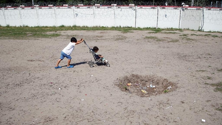 Children play at a makeshift camp for migrants in Horgos, Serbia, meters away from Serbia's border with Hungary, Thursday, Aug. 25, 2016. Officials say Hungary's police could join the Serbian troops patrolling the Balkan country's border with Macedonia or Bulgaria to help curb the influx of migrants trying to reach the European Union. (AP Photo/Darko Vojinovic)