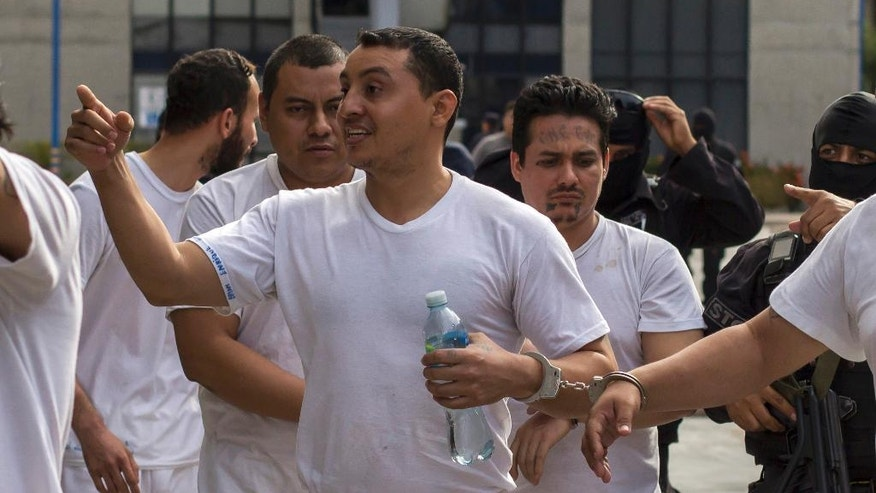 In this Tuesday, Aug. 2, 2016 photo, handcuffed to another prisoner, Marvin Quintanilla Ramos, center, an evangelical pastor accused by El Salvador Police to be the financier of Mara Salvatrucha gang, is walked out after a court hearing in San Salvador, El Salvador. Prosecutors allege that Ramos used his pastoral credentials to access prisons so he could conspire with jailed leaders of the gang. Religion, they say, was a facade to mask his real work: helping run Mara Salvatrucha's street operations and directing its finances at a key moment when gangs are facing a tough crackdown by the government and are moving to diversify their criminal operations and become more corporate in makeup and structure. (AP Photo/Salvador Melendez)