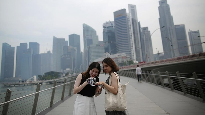 Tourists look at photographs taken on their smartphones in front of a hazy financial skyline on Friday, Aug. 26, 2016 in Singapore. Singapore's air quality deteriorated to unhealthy levels on Friday as winds blew smoke from fires on Sumatra across the city-state and southern Malaysia. (AP Photo/Wong Maye-E)