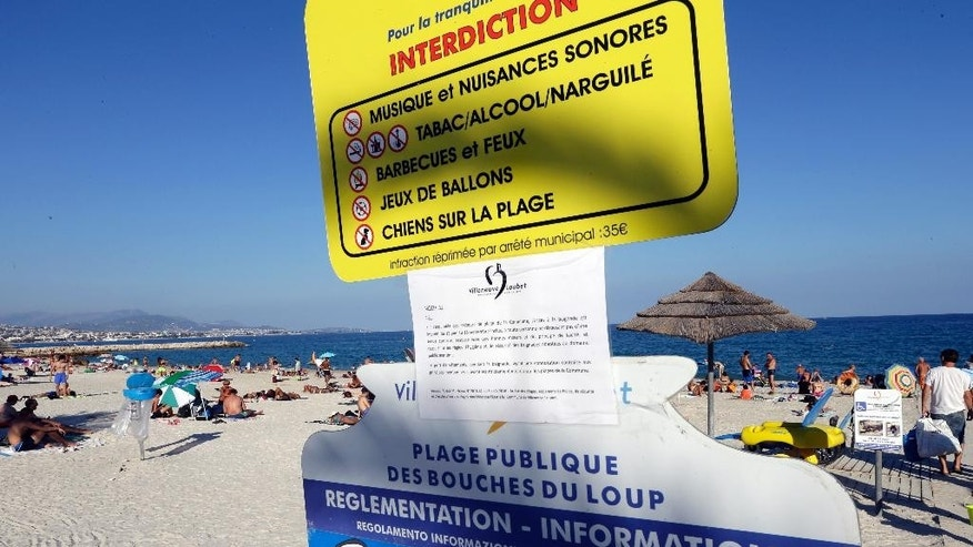A bylaw forbidding women to wear burkini is posted on an information panel at a public beach in Villeneuve-Loubet, French Riviera, southern France, Friday, Aug. 26, 2016. France's top administrative court has overturned Villeneuve-Loubet's burkini ban amid shock and anger worldwide after some Muslim women were ordered to remove body-concealing garments on French Riviera beaches. (AP Photo/Claude Paris)