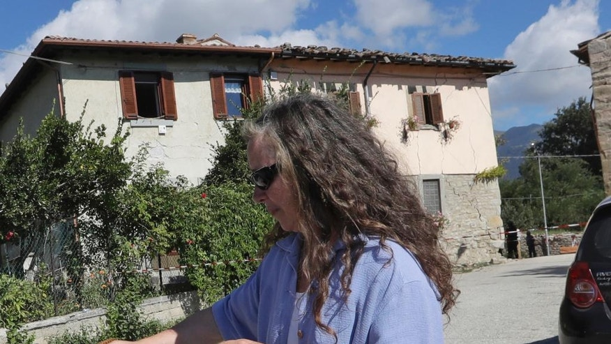 Giancarla Pomponi stands outside her damaged family villa in Sant'Angelo, near Amatrice, central Italy, Thursday, Aug. 25, 2016 after an earthquake. Pomponi was near tears as firefighters walked gingerly through the home Thursday afternoon to retrieve a few essential items: ID papers, an oxygen machine, some gold and checkbooks. (AP Photo/Alessandra Tarantino)
