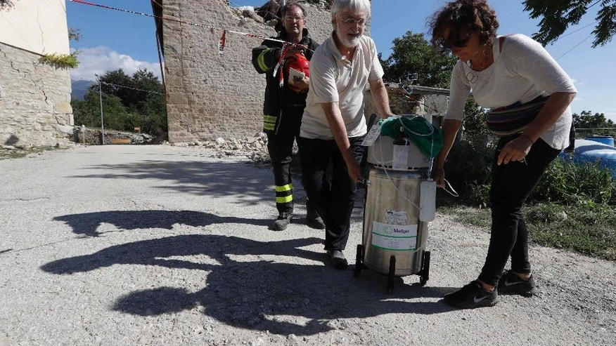Carlo Sadich, center, carries medical equipment outside his damaged family villa with the help of Italian firefighter head team Rossano Riglioni, left, in Sant'Angelo, near Amatrice, central Italy, Thursday, Aug. 25, 2016. Rustic yet refined, the two-story villa at the foothills of the Apennines is a family treasure, embracing five centuries of the Celli family's noble history, memories and mementoes. But after the earthquake left wide cracks in the exterior walls, the latest generation wonders if they'll ever set foot inside again.  (AP Photo/Alessandra Tarantino)