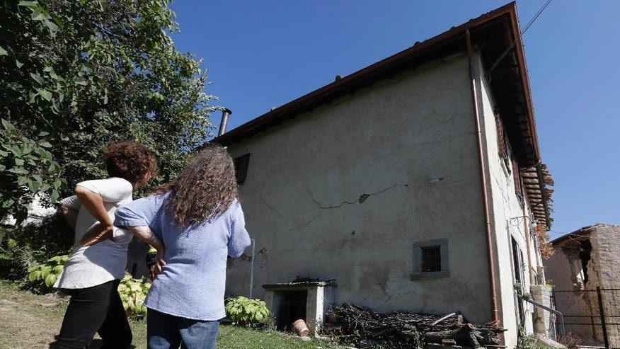 Giancarla Pomponi, right, looks at her damaged family villa, in Sant'Angelo, near Amatrice, central Italy, Thursday, Aug. 25, 2016. Pomponi was near tears as firefighters walked gingerly through the home Thursday afternoon to retrieve a few essential items: ID papers, an oxygen machine, some gold and checkbooks. (AP Photo/Alessandra Tarantino)
