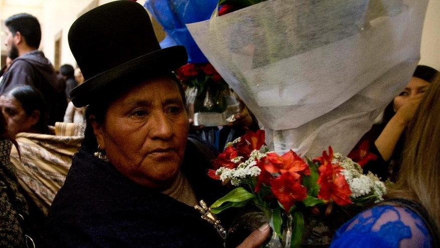 An Aymara woman arrives with a bouquet of flowers to leave for Bolivia's late Deputy Minister of Internal Affairs Rodolfo Illanes, at the government palace in La Paz, Bolivia Friday, Aug. 26, 2016. Striking Bolivian miners kidnapped and beat to death Illanes Thursday, in a shocking spasm of violence following weeks of tension over dwindling paychecks in a region hit hard by falling metal prices. The miners were demanding they be allowed to work for private companies, who promise to put more cash in their pockets. (AP Photo/Juan Karita)