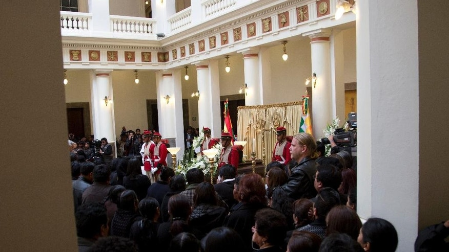 Mourners gather before the coffin containing the remains of Bolivia's Deputy Minister of Internal Affairs Rodolfo Illanes, during a Mass inside the government palace in La Paz, Bolivia Friday, Aug. 26, 2016. Striking Bolivian miners kidnapped and beat to death Illanes Thursday, in a shocking spasm of violence following weeks of tension over dwindling paychecks in a region hit hard by falling metal prices. The miners were demanding they be allowed to work for private companies, who promise to put more cash in their pockets. (AP Photo/Juan Karita)