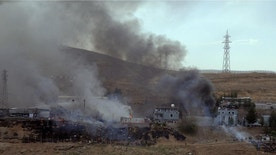 Smoke rises and fires still burn after Kurdish militants attacked a police checkpoint in Cizre, southeast Turkey, Friday, Aug. 26, 2016, with an explosives-laden truck, killing several police officers and wounding dozens more, according to reports from the state-run Anadolu news agency. The attack struck the checkpoint some 50 meters (yards) from a main police station near the town of Cizre, in the mainly-Kurdish Sirnak province that borders Syria. Turkish authorities have put a temporary ban on distribution of images relating to Friday's Cizre attack within Turkey. (IHA via AP)
