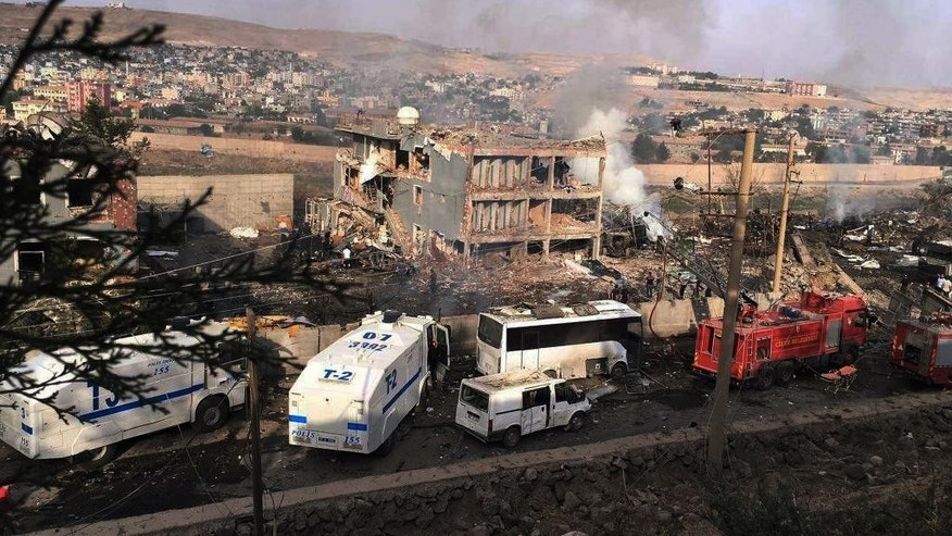 Smoke still rises from the scene after Kurdish militants attacked a police checkpoint in Cizre, southeast Turkey, Friday, Aug. 26, 2016, with an explosives-laden truck, killing several police officers and wounding dozens more, according to reports from the state-run Anadolu news agency. The attack struck the checkpoint some 50 meters (yards) from a main police station near the town of Cizre, in the mainly-Kurdish Sirnak province that borders Syria. Turkish authorities have put a temporary ban on distribution of images relating to Friday's Cizre attack within Turkey. (DHA via AP)