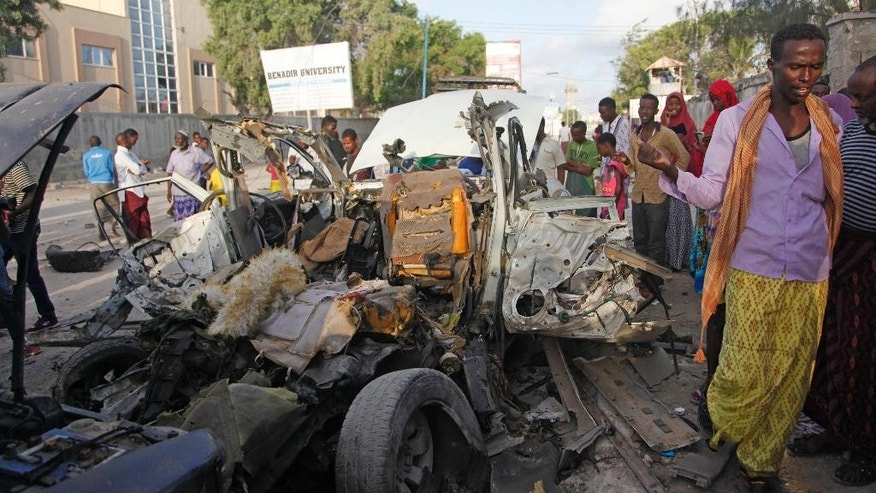 Somalis gather near the wreckage of a car used during an overnight car bomb attack outside a beachfront restaurant in Mogadishu, Somalia, Friday Aug, 26 ,2016. Somalia police say that security forces have ended an overnight siege of a beach restaurant by al-Shabab gunmen in which eight people were killed.(AP Photo/Farah Abdi Warsameh)