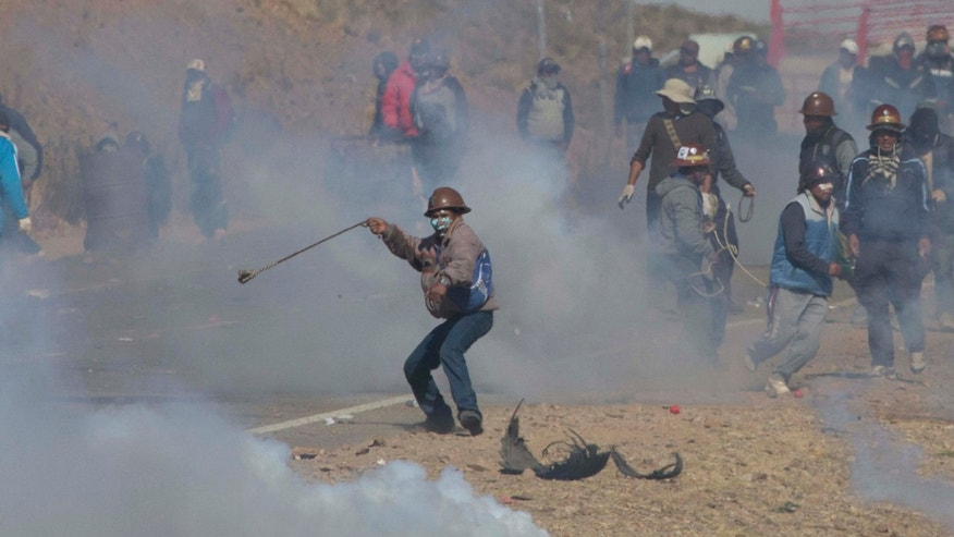 Aug. 25, 2016: Independent miners clash with the police as they run from clouds of tear gas during protests in Panduro, Bolivia.