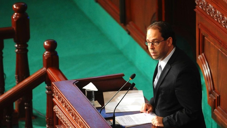 Newly named Tunisian Prime Minister Youssef Chahed, center, delivers his speech at f the Parliament in Tunis, Friday Aug. 26, 2016 ahead of a confidence vote. Chahed, 41, was minister for local affairs in the government of Habib Essid that fell last month. (AP Photo/Riadh Dridi)
