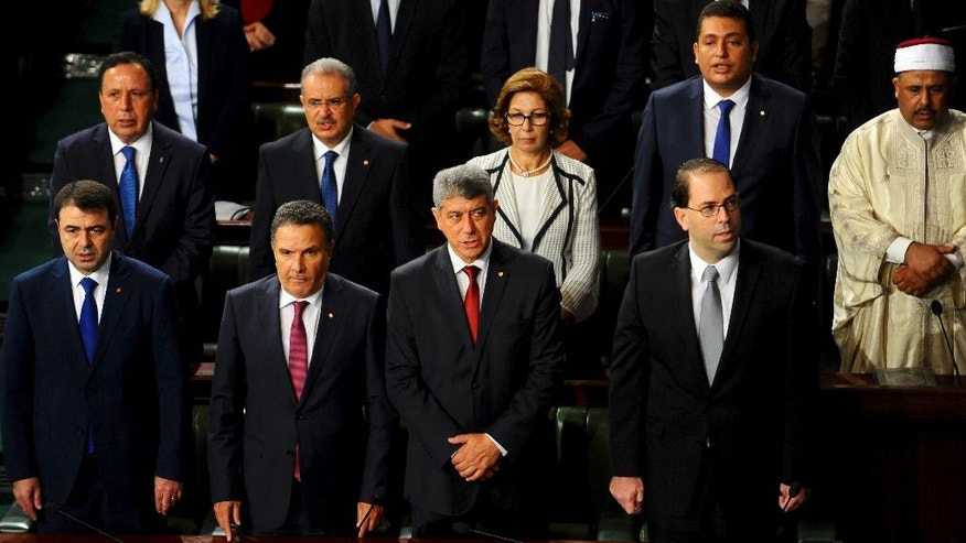 From the left, front row, Tunisian Interior Minister Hedi Mejdoub, Defense Minister Farhat Horchani, Justice Minister Ghazi Jeribi and newly named Tunisian Prime Minister Youssef Chahed, stand at the Parliament in Tunis, Friday Aug. 26, 2016 ahead of a confidence vote. Chahed, 41, was minister for local affairs in the government of Habib Essid that fell last month. (AP Photo/Riadh Dridi)