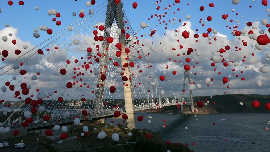 Red and white balloons, symbolising the colours of Turkish national flag,  float in the air during the inauguration of the new Yavuz Sultan Selim Bridge, the third bridge over the Bosporus, in Istanbul, Friday, Aug. 26, 2016. (Tolga Adanali, Depo Photos via AP)