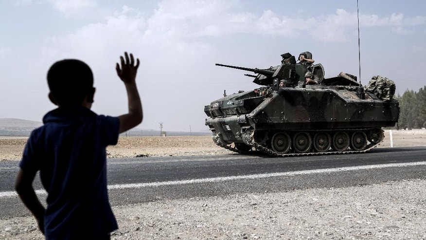 A child waves toward Turkish troops heading to the Syrian border, in Karkamis, Turkey, Friday, Aug. 26, 2016. Turkey's state-run Anadolu news agency said late Thursday Turkish artillery have shelled a group of Syrian Kurdish militia fighters in the north of the town of Mambij after they allegedly ignored warnings to retreat.  (AP Photo/Halit Onur Sandal)