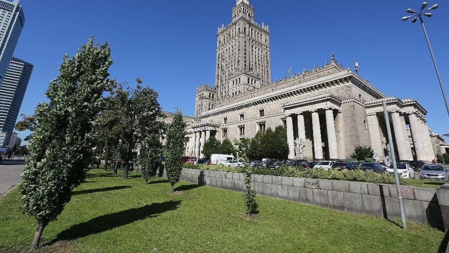 A plot of land by the landmark Palace of Culture and Science in downtown Warsaw, Poland, Friday, Aug. 26, 2016., that is at the center of a media storm over irregularities in the restitution of private property seized by the communists into private hands. Warsaw Mayor Hanna Gronkiewicz-Waltz said Friday she fired three officials for what she described as lax oversight over the town hall's decisions to return the plot, of estimated value of some $42 million, and of other property. Documents indicate the plot should not have been returned because compensation was apparently paid for it in the 1950s. (AP Photo/Czarek Sokolowski)