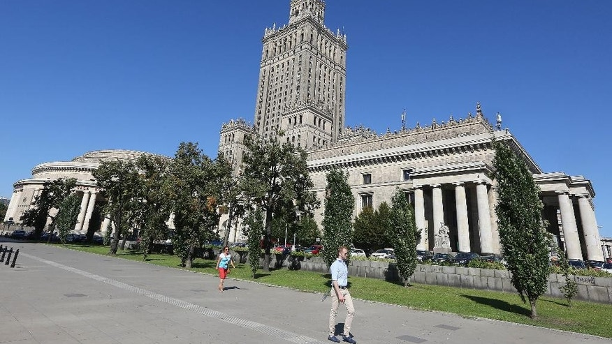 A plot of land by the landmark Palace of Culture and Science in downtown Warsaw, Poland, Friday, Aug. 26, 2016., that is at the center of a media storm over irregularities in the restitution of private property seized by the communists into private hands. Warsaw Mayor Hanna Gronkiewicz-Waltz said Friday she fired three officials for what she described as lax oversight over the town hall's decisions to return the plot, of estimated value of some US$42 million, and of other property. Documents indicate the plot should not have been returned because compensation was apparently paid for it in the 1950s. (AP Photo/Czarek Sokolowski)